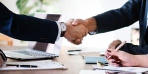 two real estate investors shaking hands over closing a deal